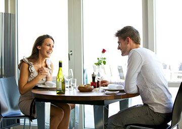 Man and woman having lunch at a restaurant with wine.