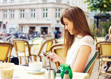 Woman texting a message at an outdoor restaurant.