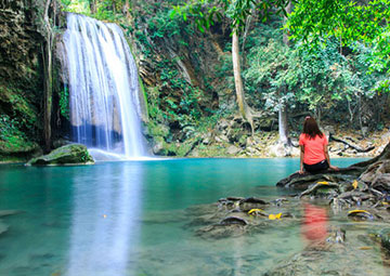 Woman sitting and watching a waterfall.