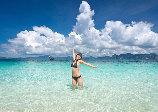 Woman posing in clear beach water.