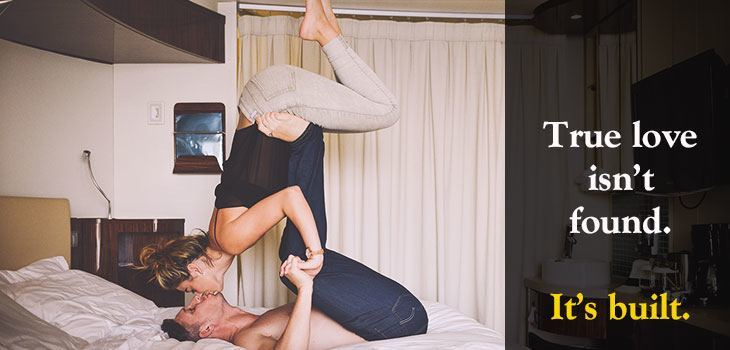 Quote: True love isn't found. It's built. Image of a couple doing yoga on a bed to demonstrate trust and chemistry. The man is holding the woman upright while kissing.