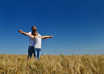 Couple spreading their arms in open field.