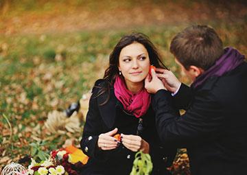 Couple sitting on grass in autumn.