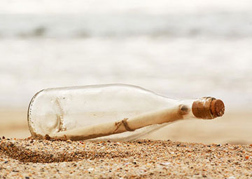 Message in the bottle lying on the beach.