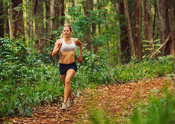 Woman running in forest trail.