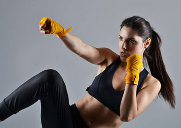 Fit woman in a kickboxing session.