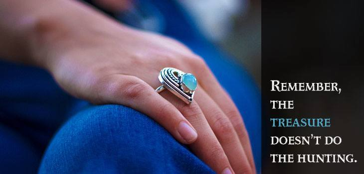 Quote: Remember, the treasure doesn't do the hunting. Image of heart-shaped ring with blue gem on a woman's hand.