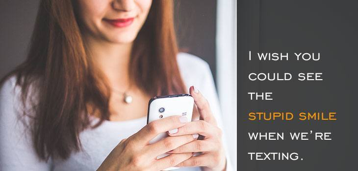 Quote: I wish you could see the stupid smile when we're texting. Image of woman smiling while she reads or texts on her phone.